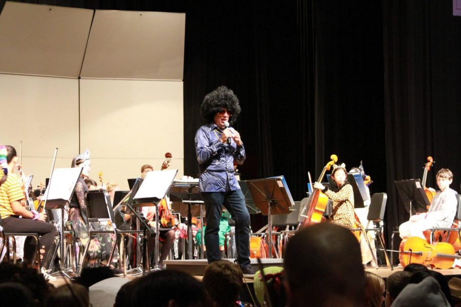 Music department head Christopher Memoli opens the concert with a speech of thanks in a groovy Halloween costume.