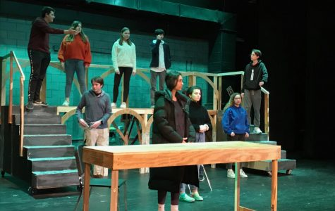 Theater Company members stand solemnly on stage at the beginning of a scene in an after school rehearsal.