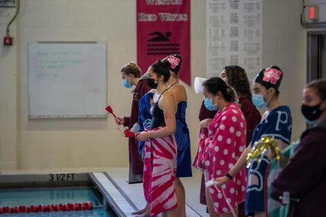 Red Tide swimmers safely watch their teammates compete in a socially-distanced meet.