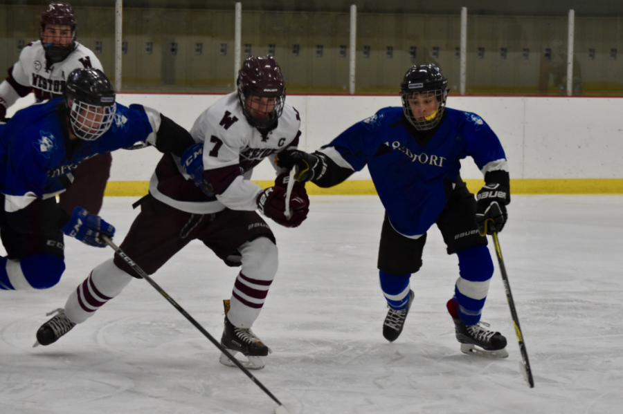 Senior Thomas Burke fights to get the puck against two Bedford defenders January 24.