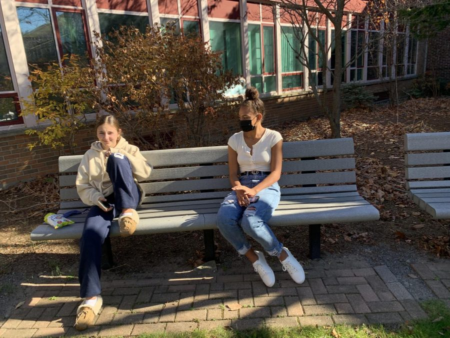 Freshmen Anke Shact and Sloan Hinton social distance outside in the WHS courtyard.